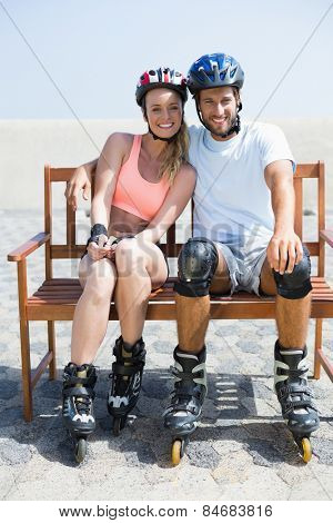 Fit couple getting ready to roller blade on a sunny day