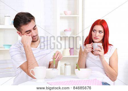 Sleepy couple has breakfast in kitchen