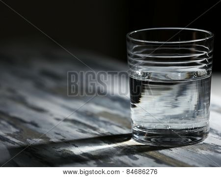 Glass of clean mineral water on old color wooden surface and dark background