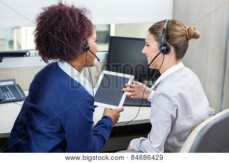 Smiling female call center employees discussing while using digital tablet in office