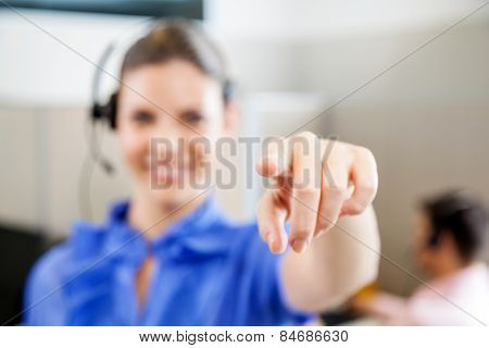 Young female customer service representative pointing at you in office