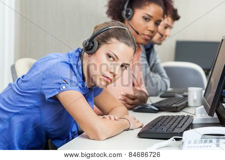 Portrait of tired female customer service representative with colleagues at desk