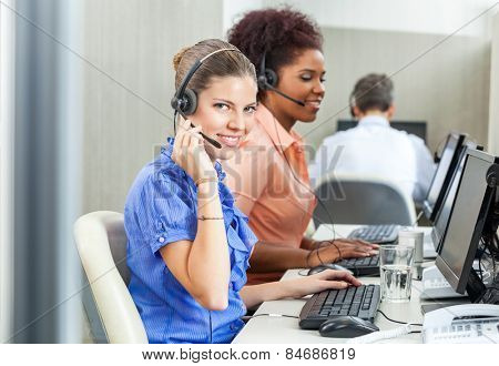 Portrait of happy young customer service representative using headset with colleagues in background at office
