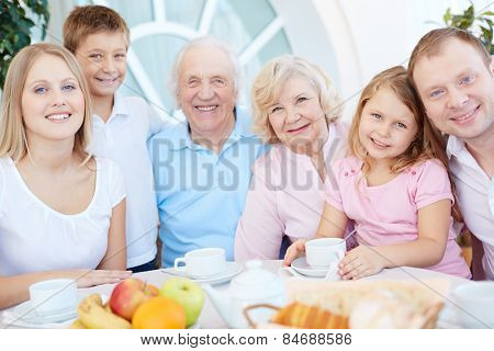 Big happy family gathered by dinner table