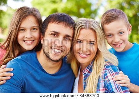 Happy parents and two adolescent children looking at camera