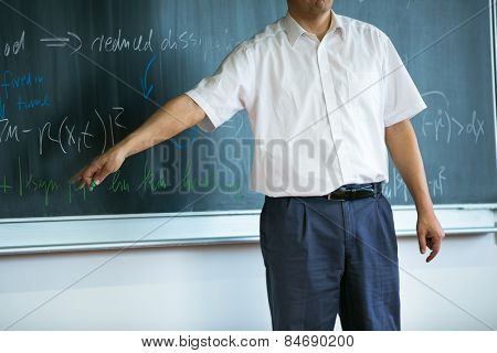 teacher teaching mathematics while pointing at blackboard in classroom