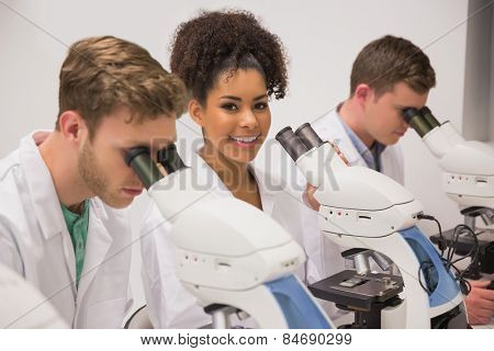 Medical students working with microscope at the university