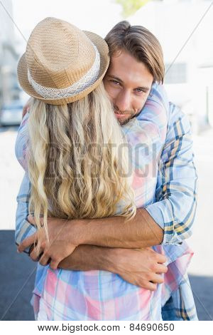 Attractive couple standing and hugging on a sunny day in the city