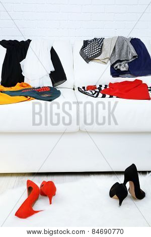 Colorful clothing on white sofa and female shoes on fluffy carpet and white brick wall background