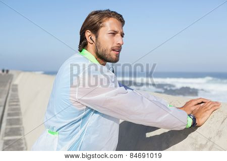 Fit man warming up on promenade on a sunny day