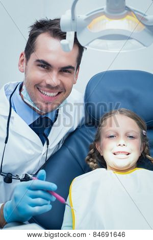 Male dentist examining girls teeth in the dentists chair