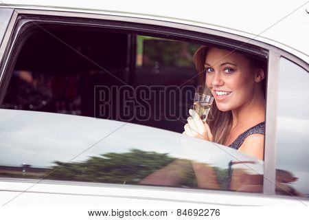 Beautiful blonde drinking champagne limousine on a sunny day
