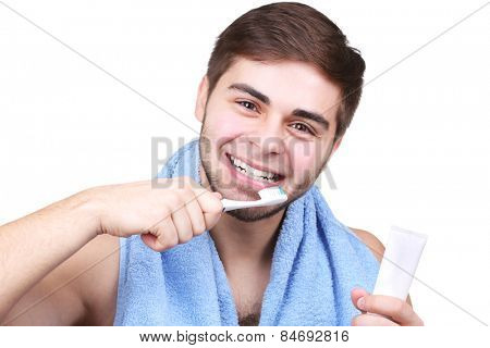 Portrait of young man with toothbrush and toothpaste in hands isolated on white
