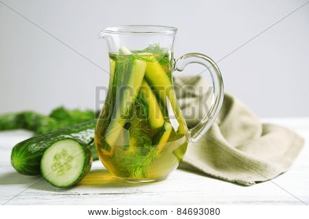 Glass ewer with fresh organic cucumber water on wooden table, on grey background