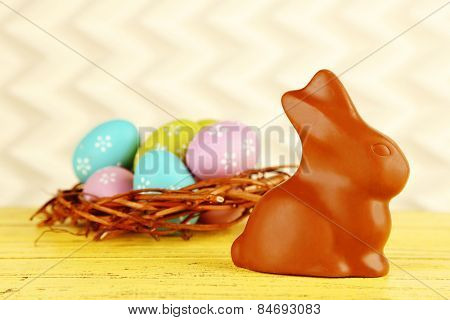 Easter composition with chocolate rabbit on light background