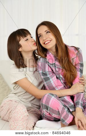 Two girls in pajamas sitting on sofa