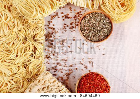 Different dry instant noodles with spices on flax background