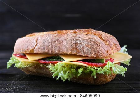 Fresh and tasty sandwiches with cheese and vegetables on wooden background