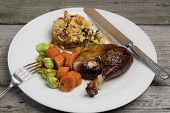 image of roast duck  - Roasted duck leg with apple and herb stuffing carrots and Brussels sprouts - JPG