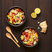 pic of sweet-corn  - Overhead shot of two bowls of fresh vegetable salad made of sweet corn cherry tomato cucumber red onion red pepper chives with toasted bread on the side photographed on dark wood with natural light - JPG