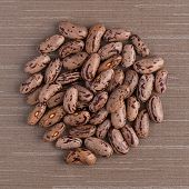 foto of pinto bean  - Top view of circle of pinto beans against brown vinyl background - JPG