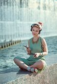 image of pinup girl  - Hipster fashion hipster girl in green dress listening music outdoor - JPG