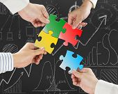 stock photo of comrades  - Group of business people assembling colorful jigsaw puzzles on business concept doodles background - JPG