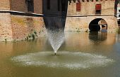 pic of castello brown  - The fountain in the moat of the medieval Castle Estense  - JPG