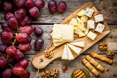 Постер, плакат: Cheese Plate: Emmental Camembert Cheese Blue Cheese Bread Sticks Walnuts Hazelnuts Honey Grap