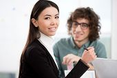 foto of she-male  - Asian beautiful young businesswoman looking at camera. She working with casual businessman. Office interior with window. Concept for teamwork ** Note: Shallow depth of field - JPG