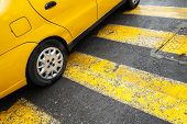 stock photo of pedestrian crossing  - Yellow taxi car stands on pedestrian crossing with lines as a road marking - JPG