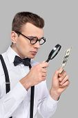 foto of bow tie hair  - Portrait of cheerful young man in bow tie and suspenders looking through magnifying glass at the dollar bill while standing against grey background - JPG