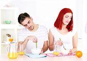stock photo of sleepy  - Sleepy couple has breakfast in kitchen - JPG