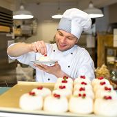 stock photo of confectioners  - Handsome confectioner in uniform decorating cakes in the pastry shop - JPG