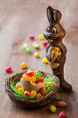 foto of easter candy  - Chocolate Easter Bunny with sweet candy on the wooden table - JPG