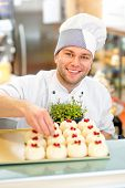 pic of confectioners  - Handsome confectioner in uniform decorating cake with currant - JPG