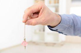 picture of pendulum  - Hand with pink crystal pendulum - JPG