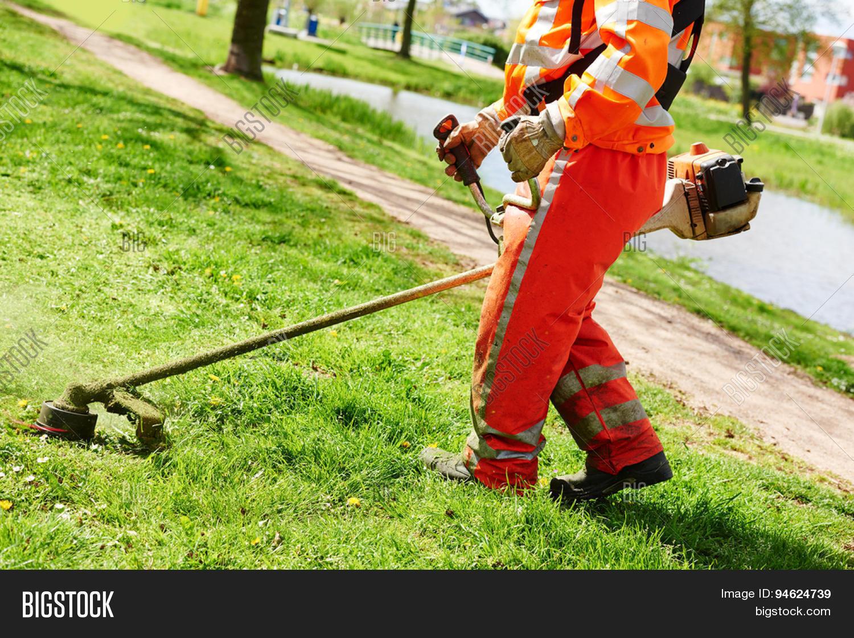 Lawn mower worker man cutting grass image photo bigstock for Lawn mower cutting grass