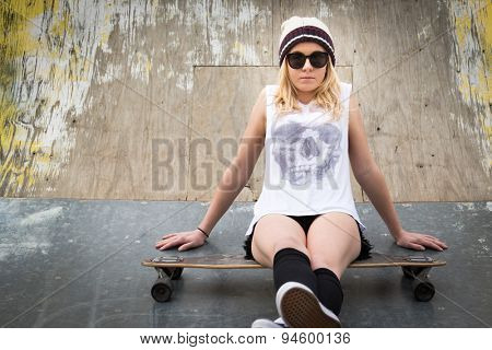 Teen skater girl sitting on skateboard