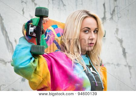 Pretty teenage girl holding skateboard