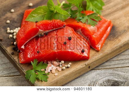 Fresh Bright Red Copper River Salmon Fillets On Rustic Wooden Server With Spices And Herbs