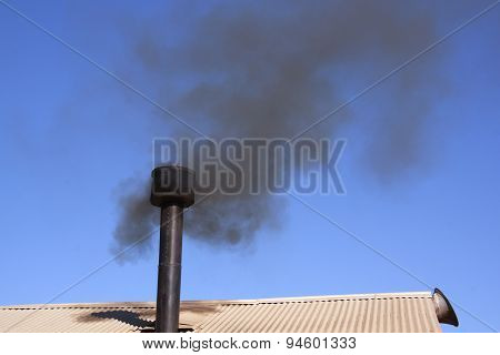 Metal Roof With Chimney Belching Black Smoke