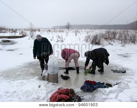 three rural women washing clothes in the ice-hole