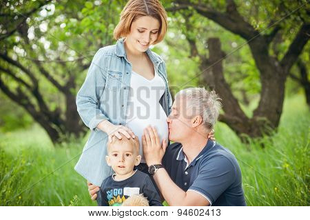 Happy family. Father kissing pregnant wife's belly.