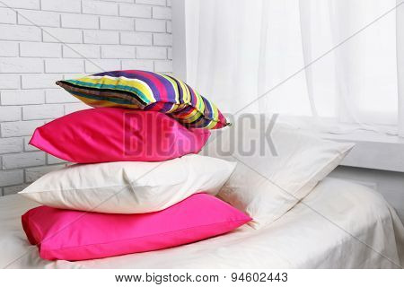 Comfortable bed with colorful pillows in bedroom