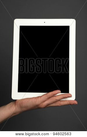 Hand holding tablet on gray background