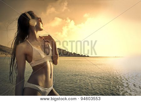 Young woman listening to music at the beach
