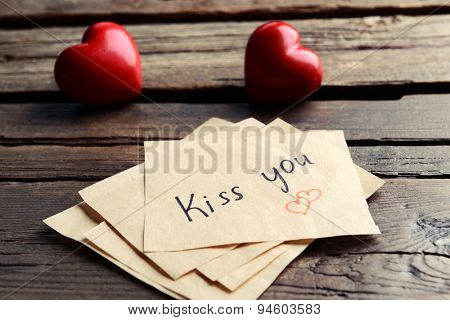Written message with decorative hearts on wooden table close up