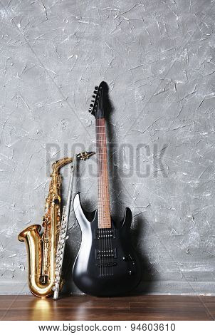 Electric guitar, flute and saxophone on gray wall background