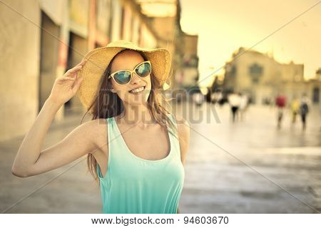Smiling blonde girl wearing sunglasses and a big hat